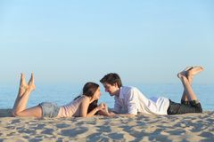 Couplez la datation et le repos sur le sable de plage Photo stock
