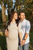 Couplez la famille dans l'attente d'un bébé étreignant dans des rayons du soleil photo stock