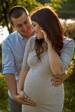 Couplez la famille dans l'attente d'un bébé étreignant dans des rayons du soleil photo libre de droits