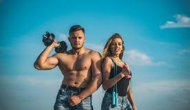 Couplez la formation concept dehors, de sport et de santé Homme avec le torse musculaire et les haltères de levage de sourire blo Photo libre de droits