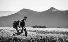 Couplez la hausse dans les belles montagnes le jour ensoleillé chaud Photos stock