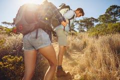Couplez la hausse en montagne un jour ensoleillé chaud image stock