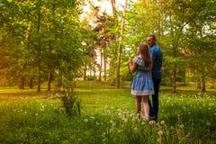 Couplez la marche au printemps jeune homme de forêt et pissenlits de soufflement de femme au coucher du soleil Photo libre de droits