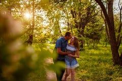 Couplez la marche au printemps jeune homme et fille de forêt étreignant et embrassant au coucher du soleil Photo libre de droits