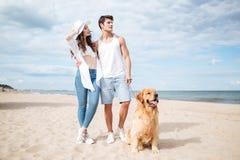 Couplez la marche avec le chien sur la plage en été Photos stock