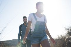 Couplez la marche dans les montagnes à la lumière du soleil Images stock