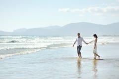 Couplez la marche en tenant des mains sur la plage de Sperlonga, Italie Photos stock
