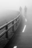 Couplez la marche le long de la route dans le brouillard Photographie stock