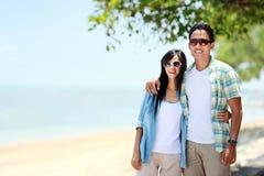 Couplez la marche par la plage ensemble dans l'amour se tenant autour de chacun Photographie stock libre de droits