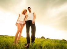 Couplez la marche par le champ et tenir des mains Images stock
