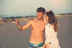 Couplez la marche sur la plage au coucher du soleil prenant la photo de selfie Photographie stock