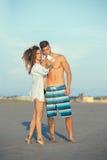 Couplez la marche sur la plage au coucher du soleil prenant la photo de selfie Photos libres de droits