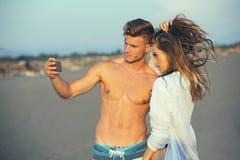 Couplez la marche sur la plage au coucher du soleil prenant la photo de selfie Images libres de droits
