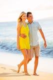 Couplez la marche sur la plage au coucher du soleil, vacances romantiques Image stock
