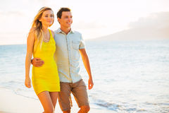 Couplez la marche sur la plage au coucher du soleil, vacances romantiques Image libre de droits