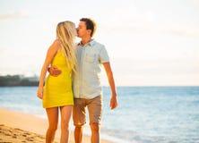 Couplez la marche sur la plage au coucher du soleil, vacances romantiques Photo stock
