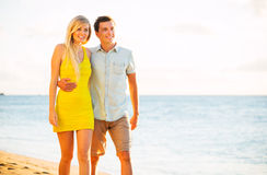 Couplez la marche sur la plage au coucher du soleil, vacances romantiques Photo libre de droits