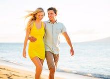Couplez la marche sur la plage au coucher du soleil, vacances romantiques Photographie stock libre de droits