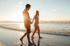 Couplez la marche sur la plage ensemble au coucher du soleil Photographie stock