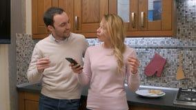 Couplez la musique de écoute ensemble et en chantant dans la cuisine, dansant ensemble Images libres de droits