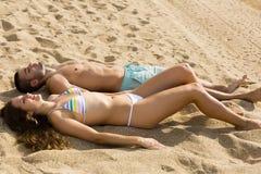 Couplez la pose sur la plage sablonneuse dans le jour ensoleillé Image stock