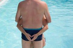Couplez la position à la femme de piscine faisant le coeur sur le dos de l'homme Photographie stock