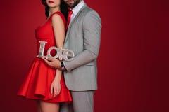 Couplez la position avec amour de signe d'isolement sur le rouge Image stock