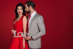 Couplez la position avec amour de signe d'isolement sur le rouge Photographie stock libre de droits