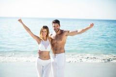 Couplez la position avec des bras tendus sur le rivage à la plage Images libres de droits