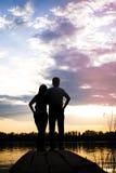 Couplez la position sur le pont sur le rivage du lac au coucher du soleil Image stock