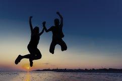 Couplez la silhouette sautant au coucher du soleil sur la plage Images stock