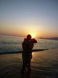 Couplez la silhouette sur la plage au coucher du soleil près de la mer Photographie stock libre de droits