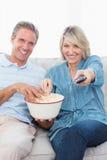 Couplez la TV de observation et maïs éclaté de consommation sur le sofa Images libres de droits