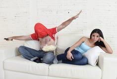 Couplez la TV de observation pour folâtrer le football avec l'homme excité en célébrant le but heureux fou et la femme ennuyée Images stock