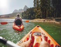 Couplez le canoë-kayak dans le lac un jour d'été Photo stock