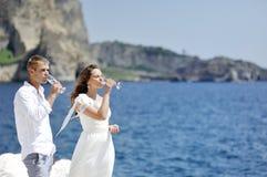 Couplez le champagne potable dans le jour du mariage près de la mer de Naples, Italie Images libres de droits