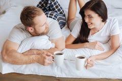 Couplez le contact visuel de maintien tout en détendant dans le lit avec du café Photographie stock libre de droits