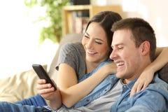 Couplez le contenu de observation riant de media dans un téléphone Photographie stock