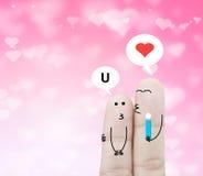 Couplez le doigt tenant la fleur et la boîte de causerie sur le bokeh rose de coeur Photographie stock libre de droits