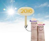 Couplez le doigt tenant le signe en bois 2016 sur le fond blanc Photo libre de droits