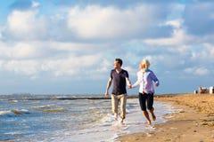 Couplez le fonctionnement par le sable et les vagues à la plage Image stock