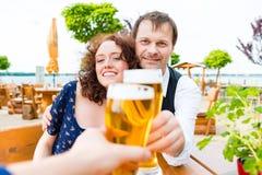 Couplez le grillage vers des amis dans le bar de jardin de bière Images stock