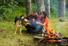 Couplez le jeu avec le chien de berger allemand près du feu, Image stock