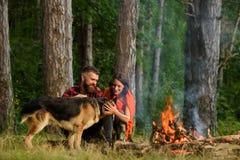Couplez le jeu avec le chien de berger allemand près du feu, Photo stock
