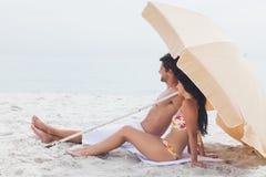 Couplez le mensonge sur la serviette de plage à la plage Photos stock