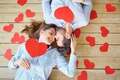 Couplez le mensonge sur le plancher en bois avec la vue de coeurs d'en haut photographie stock