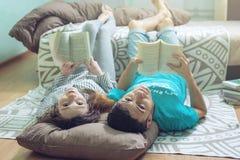 Couplez le mensonge sur le plancher et la lecture gentille de levage de jambes Photos libres de droits