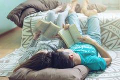 Couplez le mensonge sur le plancher et la lecture gentille de levage de jambes Photo stock