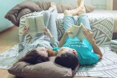 Couplez le mensonge sur le plancher et la lecture gentille de levage de jambes Image libre de droits