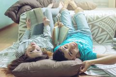 Couplez le mensonge sur le plancher et la lecture gentille de levage de jambes Photographie stock